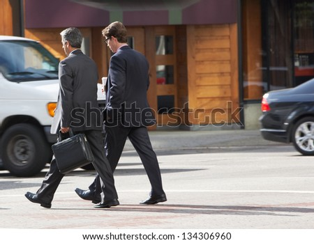 Two Businessman Chatting Whilst Crossing Street - stock photo