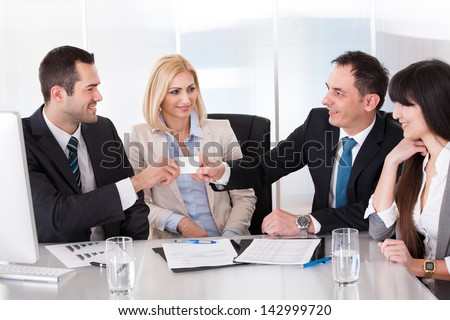 Two Businessman Exchanging Visiting Card In front Of Colleges - stock photo