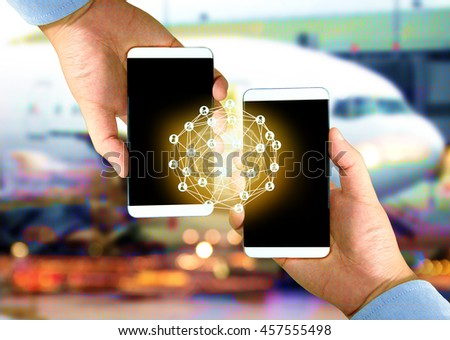 Two Businessman hands holding smartphones , Fintech concept and Peer-to-peer icon with airplane coded abstract background