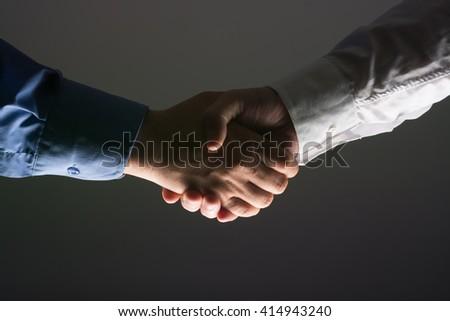 Two Businessman Handshake Handshaking between darkness and light - stock photo