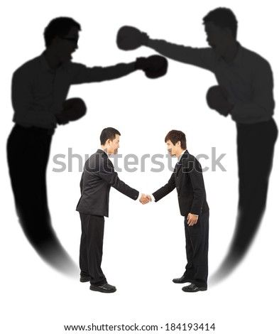 Two businessman handshake with fighting shadow - stock photo