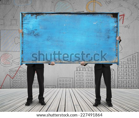 two businessman hold old blue blank wooden noticeboard stand on wooden floor with doodles wall background - stock photo