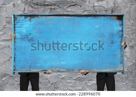 two businessman holding old blue empty wooden noticeboard on rough concrete wall background - stock photo