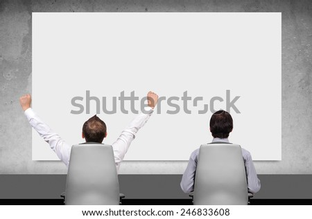 two businessman in boardroom and looking on blank poster - stock photo
