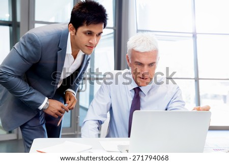 Two businessman in office having discussion in front of computer - stock photo