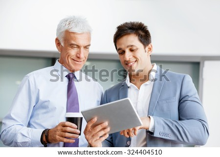 Two businessman in office with devices - stock photo