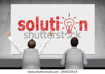 two businessman looking on poster with drawing solution - stock photo