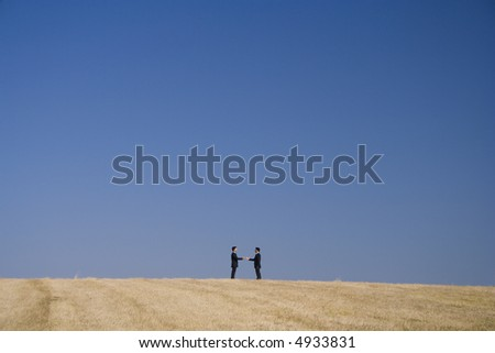 two businessman making a deal in a landscape - stock photo