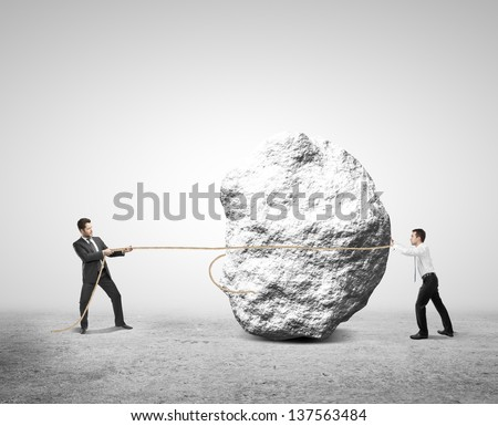 two businessman pulling a rope rock - stock photo