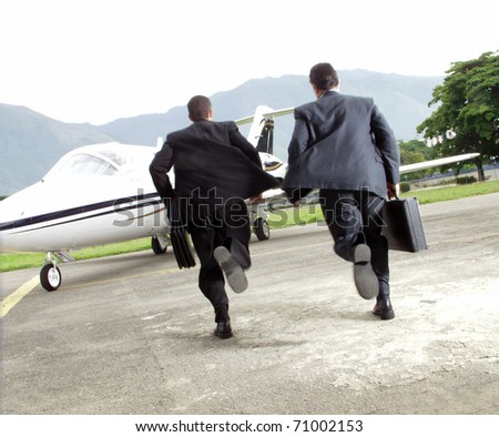 Two businessman running towards a plane. - stock photo