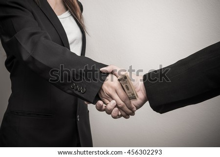 Two businessman shaking hand with money.