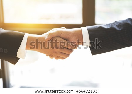 two businessman shaking hands beside window - business teamwork, cooperation concept