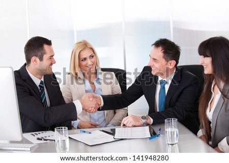 Two Businessman Shaking Hands In front Of Colleges - stock photo