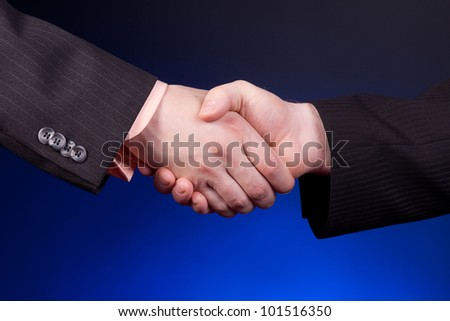 two businessman shaking hands over blue background - stock photo