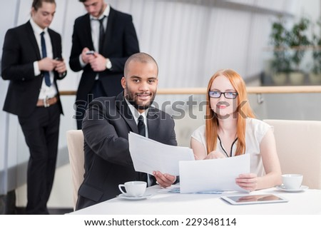 Two businessman sitting at the table and discussing business documents and keep in his hands and looking into the camera while their colleagues standing in the background and shake hands - stock photo