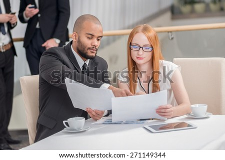 Two businessman sitting at the table and discussing business while their colleagues standing in the background and shake hands - stock photo