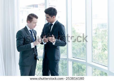 two businessman talking with mobile phone