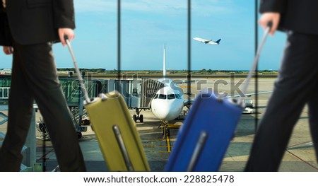 two businessman walking travel bag by an airport