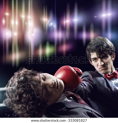 Two businessman with boxing gloves in the ring fighting with each other