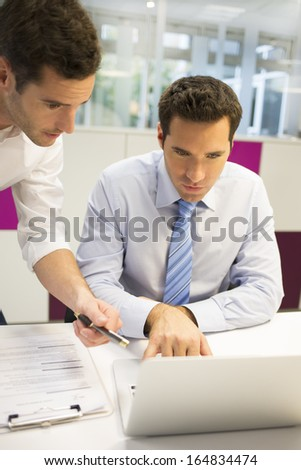 Two businessman work in office on laptop