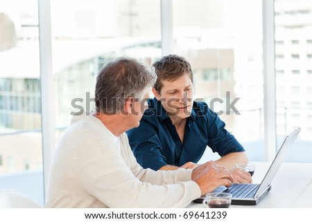 Two businessman working on their laptop in a office - stock photo