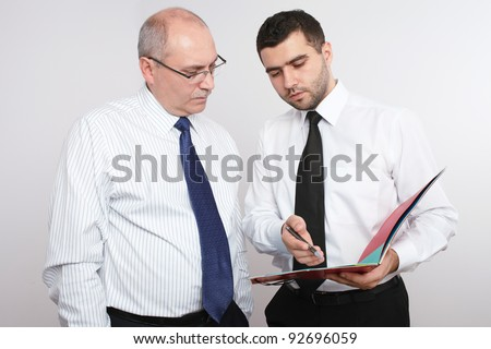 Two businessman, young and mature one discuss something. - stock photo