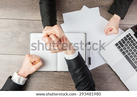 Two businessmen and businesswomen  press hands each other Armwrestling. White paper, where you can place your text or information. Business negotiations and confrontation. Top view - stock photo