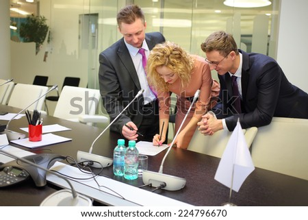 Two businessmen and secretary corrected papers in the conference hall - stock photo