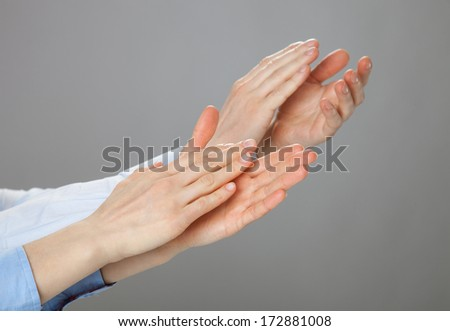 Two businessmen applauding - closeup shot on grey background