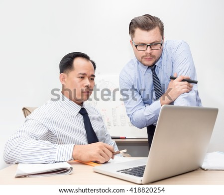 two businessmen asian and caucasian looking at laptop monitor. Graphs and diagrams on marker board in background. Teamwork, communication, brainstorming concept - stock photo