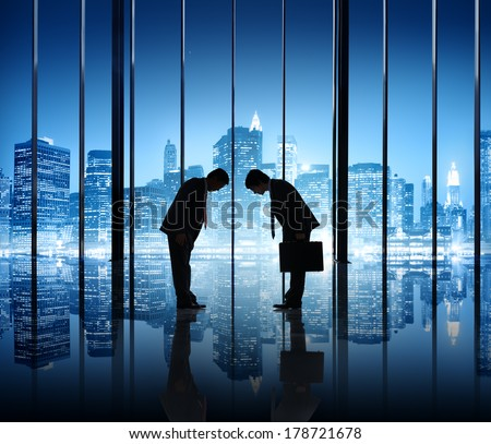 Two Businessmen Bowing in Office with City Lights - stock photo