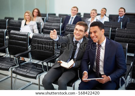 Two businessmen communicating at seminar on background of their colleagues - stock photo