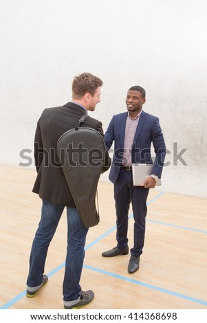 Two businessmen communicating before playing in squash on court. Happy men discussing business questions after work.