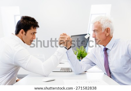 Two businessmen competeting arm wrestling in office - stock photo