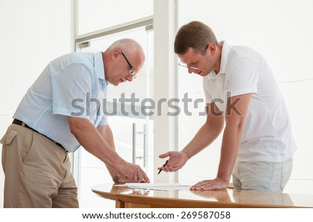 Two businessmen discussing a joint project during teamwork - stock photo