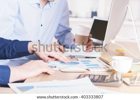 Two businessmen discussing business chart over coffee in office