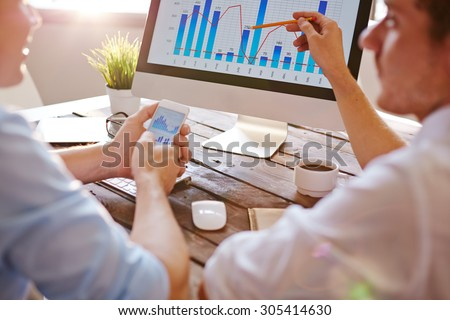 Two businessmen discussing chart on computer monitor in office - stock photo