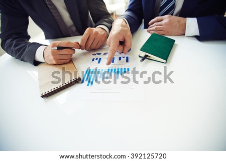 Two businessmen discussing charts at the table - stock photo