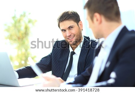 Two businessmen discussing tasks sitting at office table. - stock photo