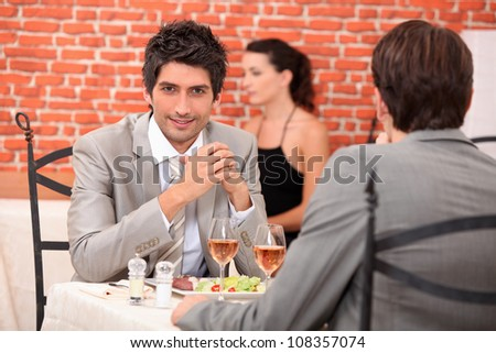 two businessmen eating in a restaurant - stock photo