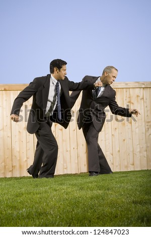 Two businessmen fighting on lawn