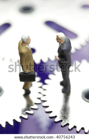two businessmen figurines standing on cogwheels, financial deal concept - stock photo