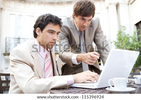 Two businessmen focused on having a meeting while sitting in a classic coffee shop terrace, using a laptop computer. - stock photo