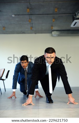 Two businessmen getting ready for corporate race - rat race concept - stock photo