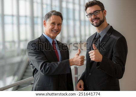 Two businessmen giving a thumbs-up - stock photo