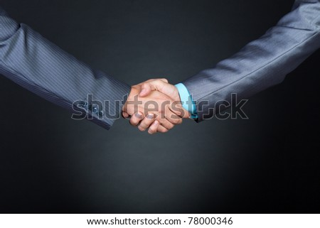Two businessmen hands in elegant suits handshake over gray dark background. Communication, greeting, agree, congratulation meeting concept.
