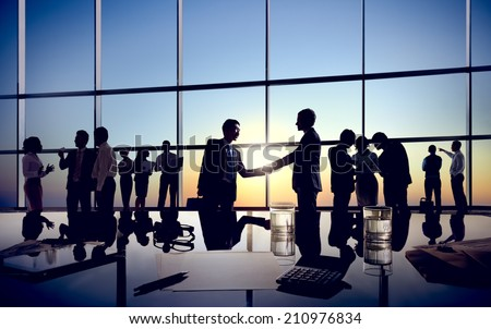 Two Businessmen Handshaking Together with Their Colleagues - stock photo