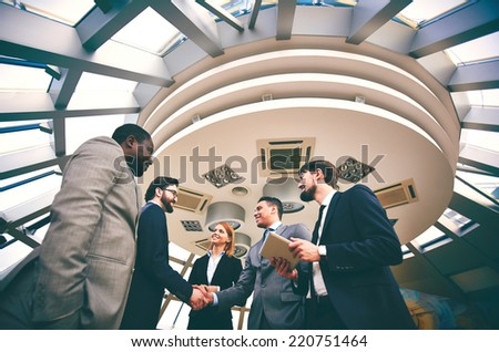 Two businessmen handshaking while their colleagues near by looking at them at meeting - stock photo