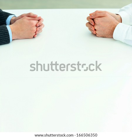 Two businessmen having a discussion. Closeup image of their hands on the table - stock photo