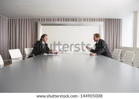 Two businessmen having a discussion in conference room - stock photo